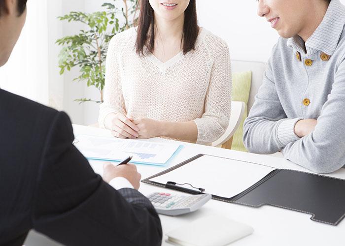 書類を見ながら話し合うスタッフと男女
